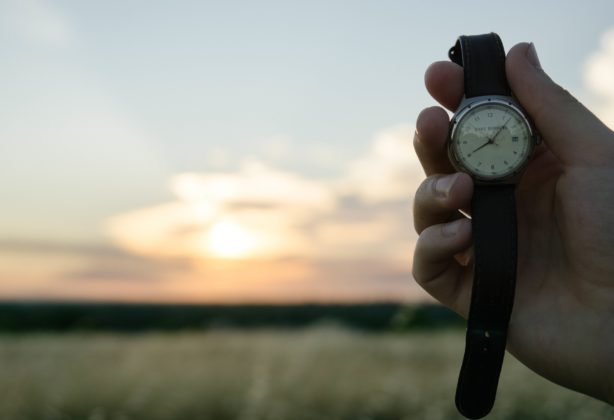 Person holding a watch with sunset in the background