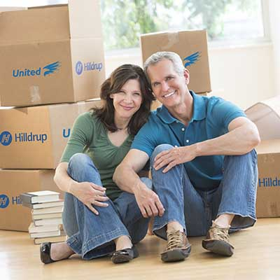 Empty nesters with moving boxes behind them