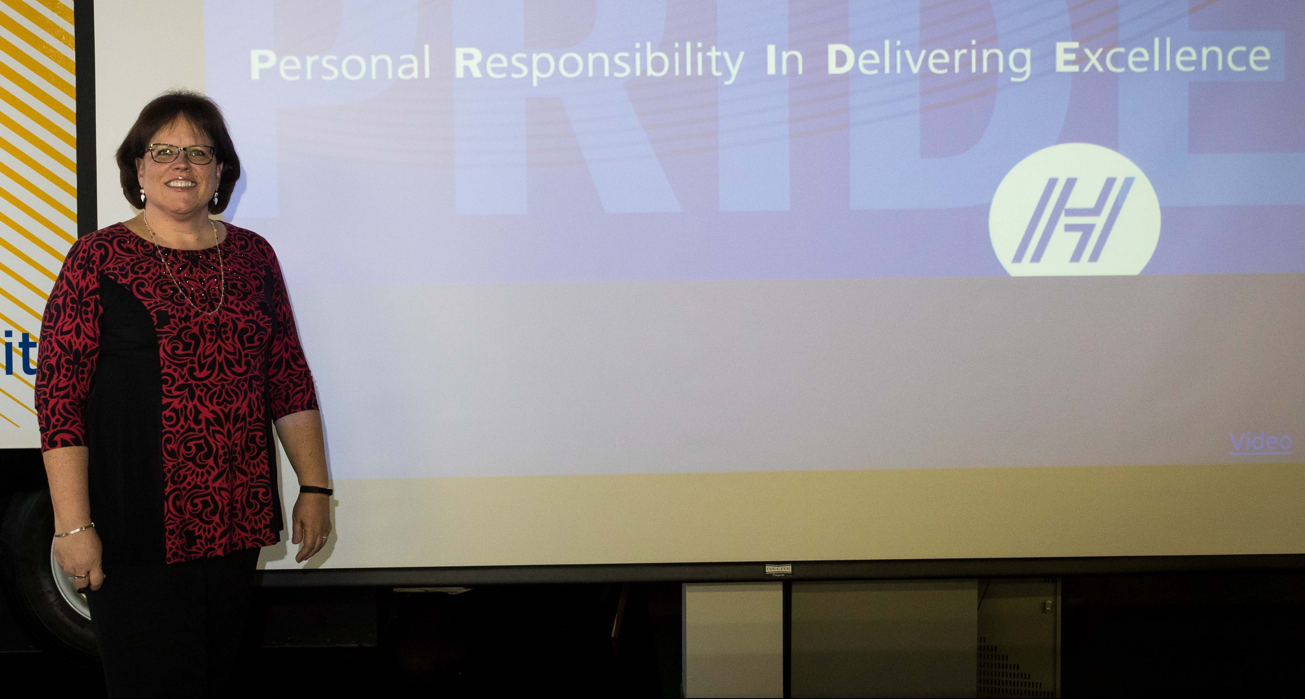 Sandy Schaaf next to powerpoint presentation