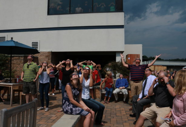 Employees water solar eclipse through special sunglasses