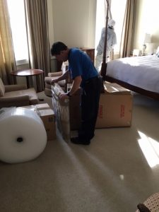 Movers pack items in a bedroom
