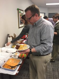 Employees enjoy a potluck for St. Patrick's Day