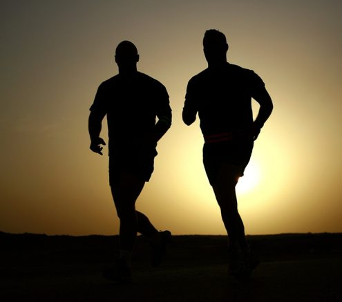 Two men running at sunrise