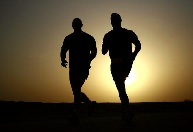 Two men running at sunrise