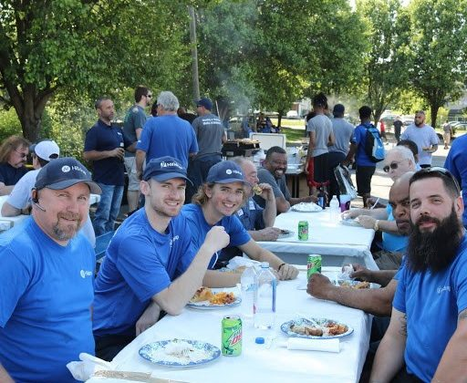 Group of Hilldrup Operations employees enjoy food at picnic table