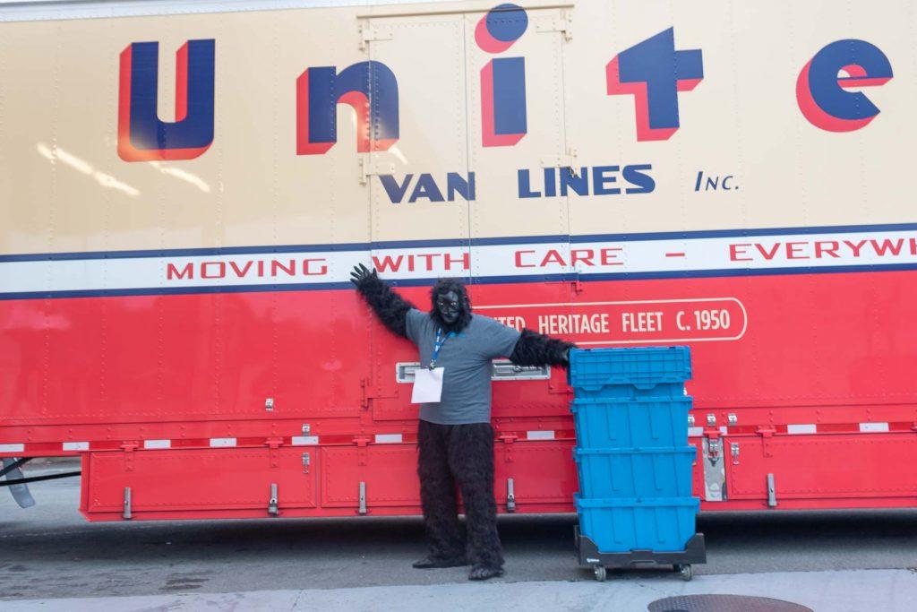 Tom Hinkley in gorilla suit posing in fron of United Van Lines moving truck