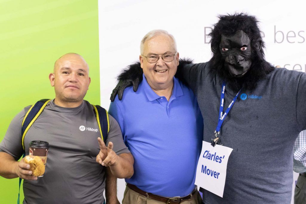 Melvin Funes, Barry Dodson, and Tom Hinkley dressed in a gorilla suit posing for a picture