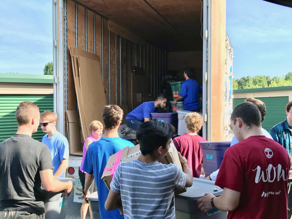 Students load bins into a Hilldrup truck
