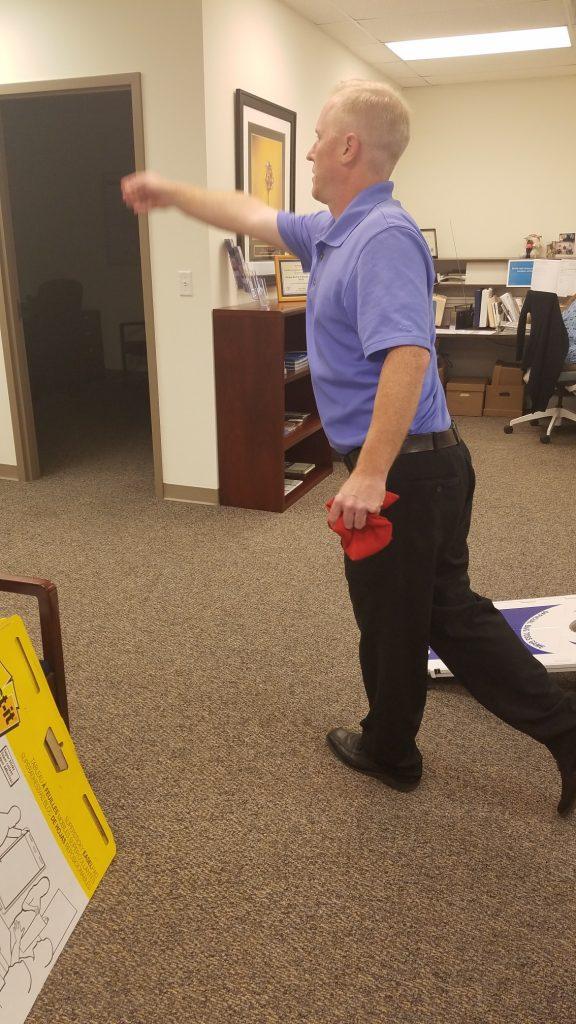 Employee throws cornhole bag