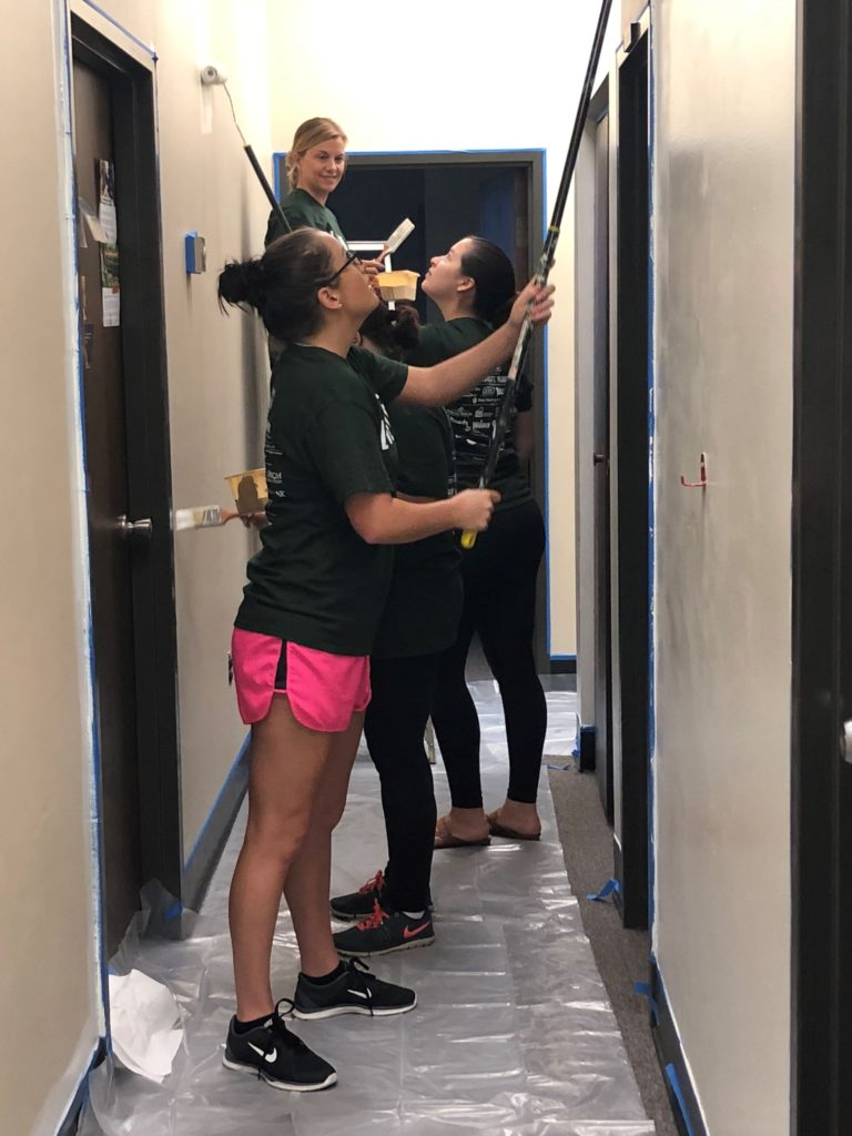 Hilldrup employees paint hallway together