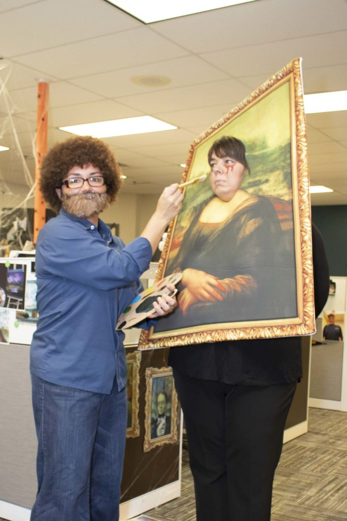 Two Hilldrup employees - one dressed as Bob Ross and another as a painting