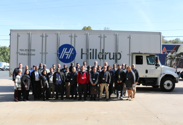 U.S. State Department visitors photographed next to Hilldrup truck