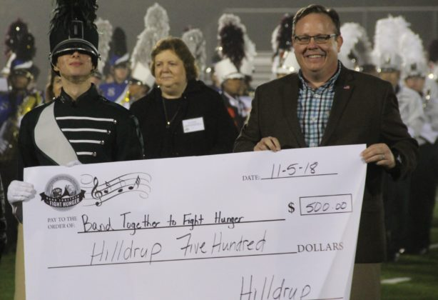 John Lohmeyer with band students and check with donated amount