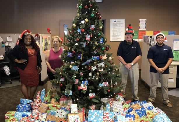 Hilldrup Orlando team around decorated Christmas tree and presents