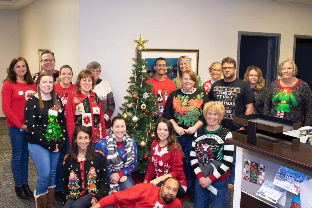 Hilldrup Stafford wears tacky sweaters by Christmas tree in office
