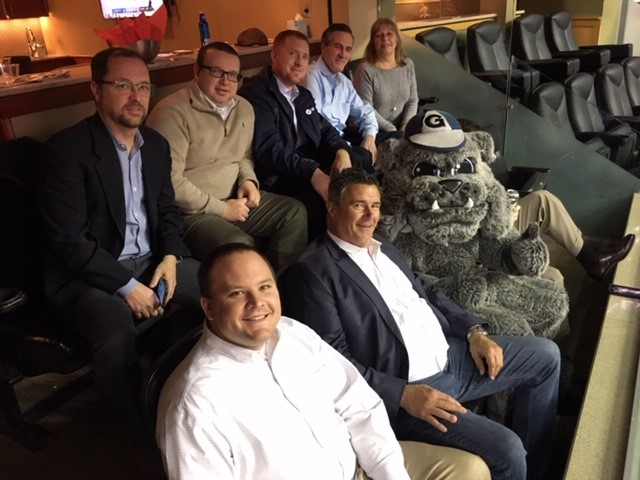 Hilldrup commercial team seated at Georgetown game with mascot