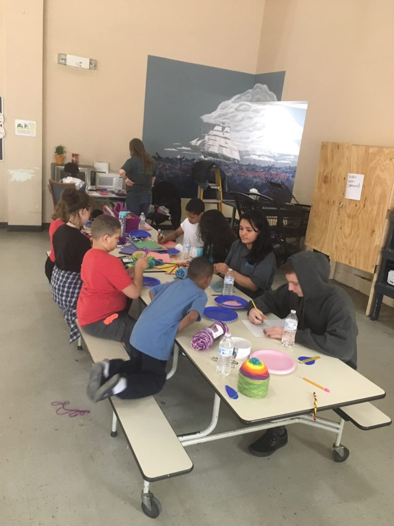 Children at the homeless shelter enjoy crafts together at a table