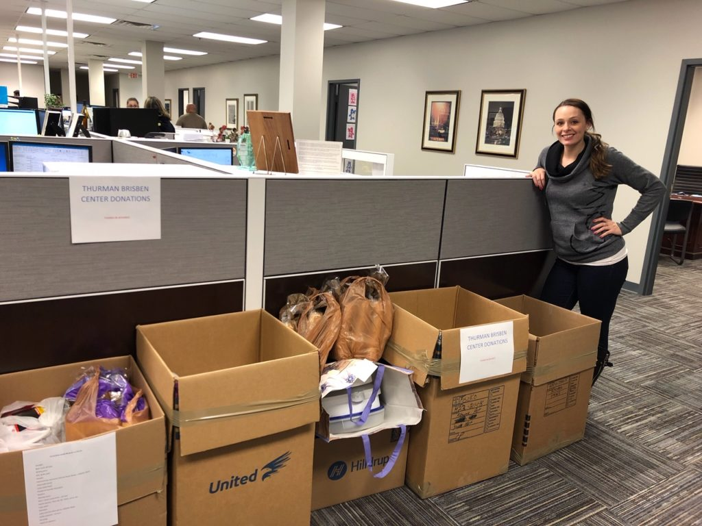 Lindsi Smith stands next to boxes of donations for homeless shelter