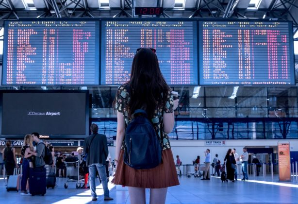 Girl standing back facing the camera in an airport toward the flight information display system