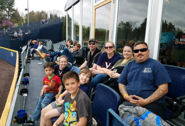 Group photo of Hilldrup employees and their kids in the club seats at UVA versus Miami baseball game