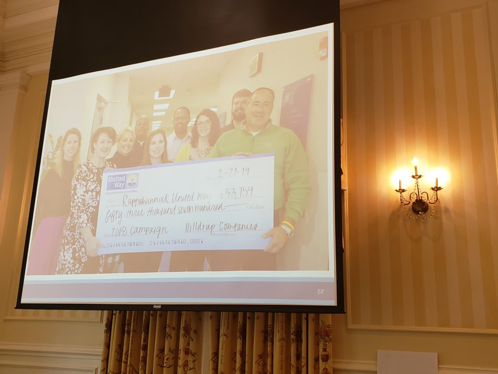 A powerpoint slide showing Hilldrup Stafford employees with our check of money raised throughout the campaign.
