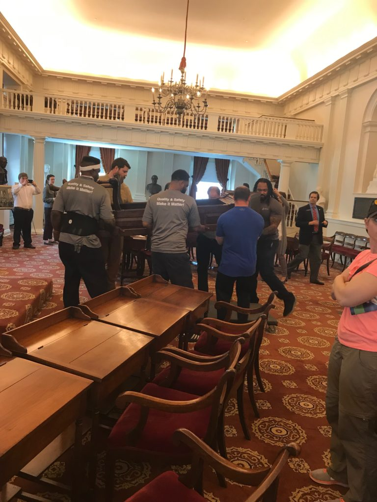 Hilldrup movers carefully moving 300 year old speakers chair into the Old House Chamber at the state capitol in Richmond