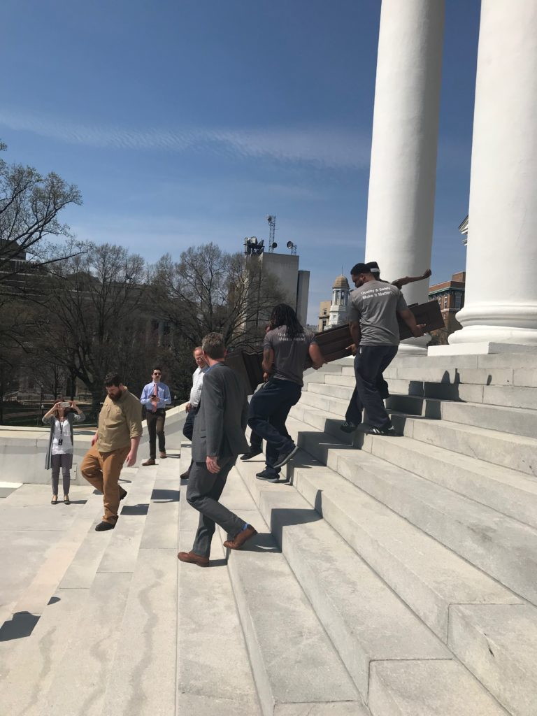 Hilldrup movers carefully carrying the Virginia relic down the stairs