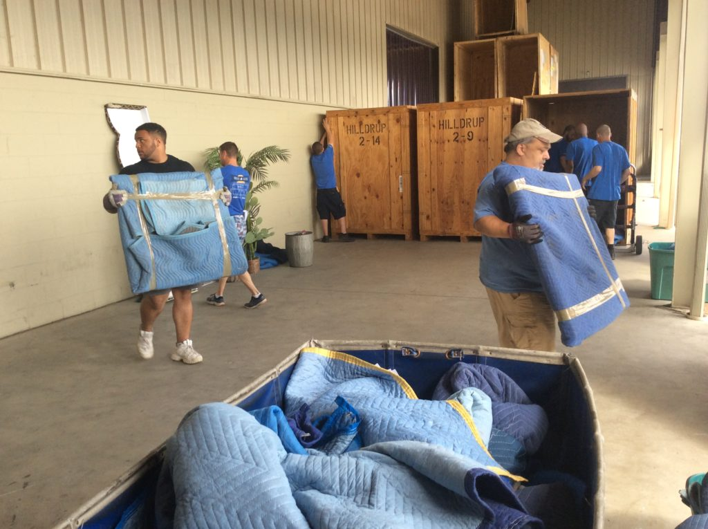 Hilldrup employees transporting picture frames wrapped in blankets to moving trucks
