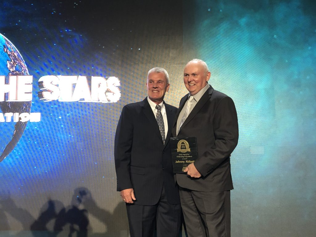 Johnny Abbott and Randy Rantz posing for a photo with award