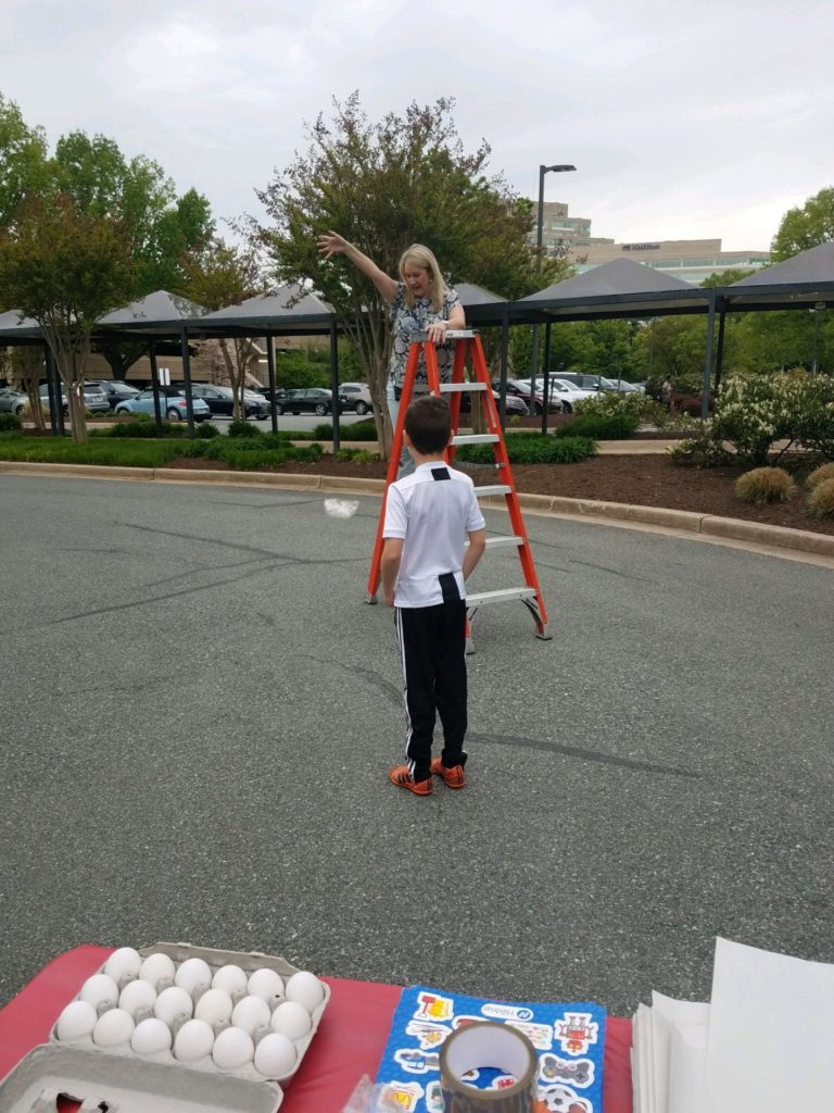 Hilldrup employees dropping an egg from the top of a ladder during a fun activity