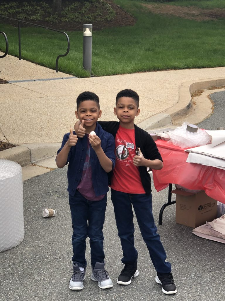 Two kids holding an egg with thumbs up