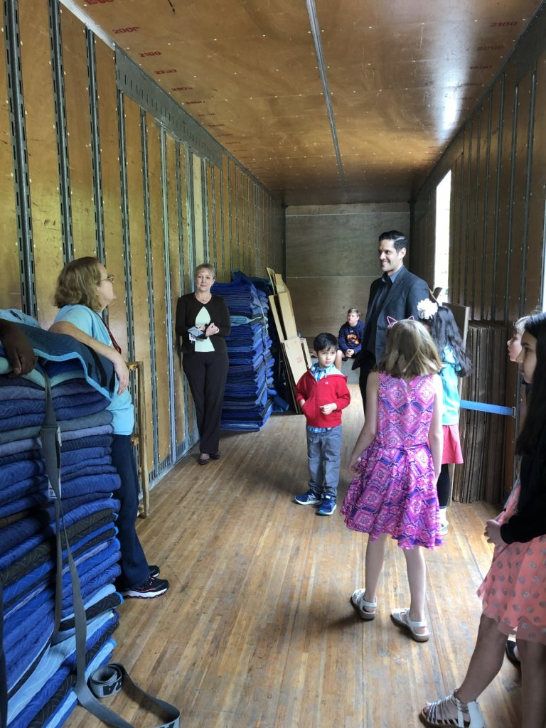Hilldrup employees showing their kids the inside of a moving truck
