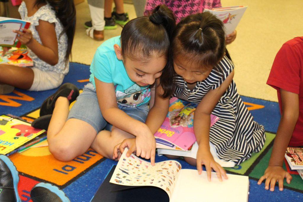 Two little girls reading