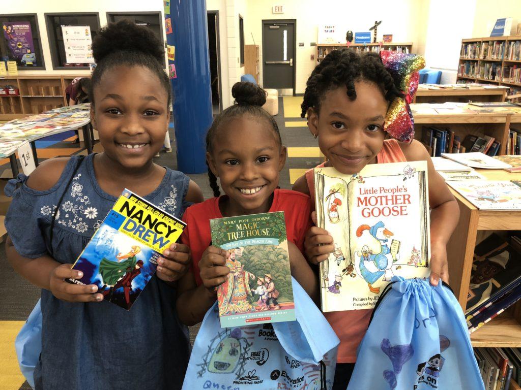 Three girls holding up books smiling