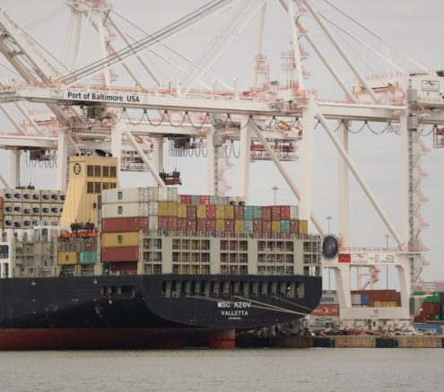 Shipping containers being loaded onto cargo ship at shipping terminal in Baltimore