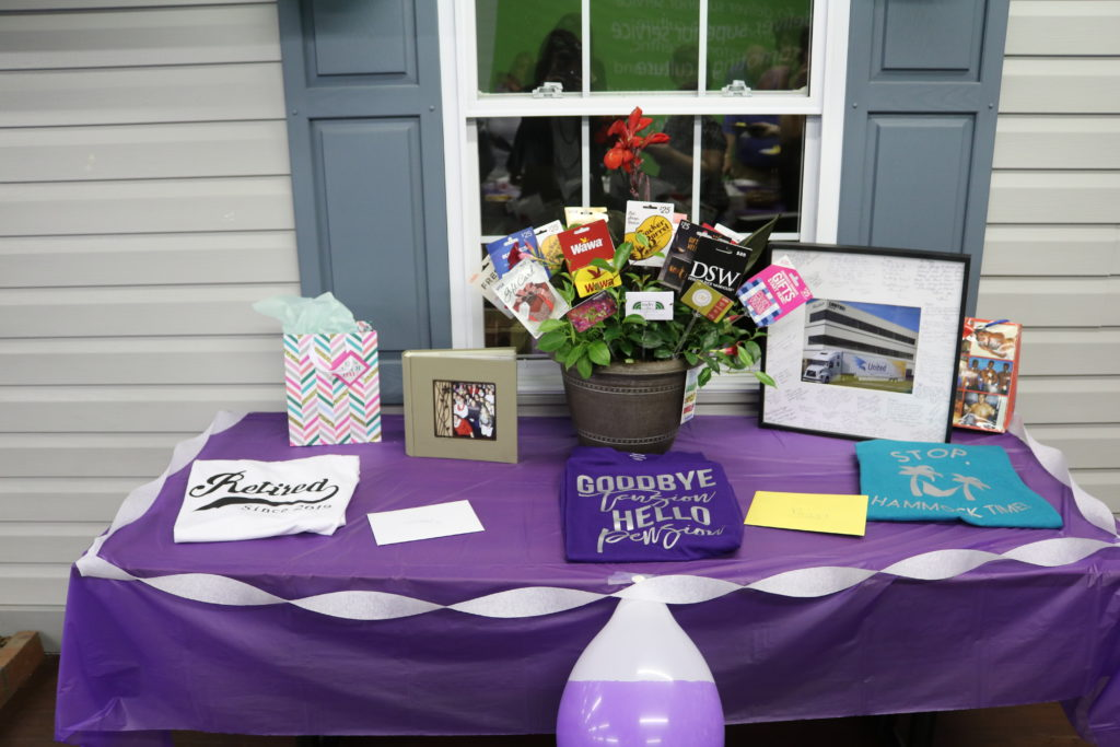 Decorated purple table with t shirts, pictures, a gift card flower pot for the retires of domestic billing