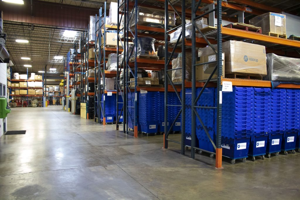 Storage warehouse with blue plastic bins and moving boxes