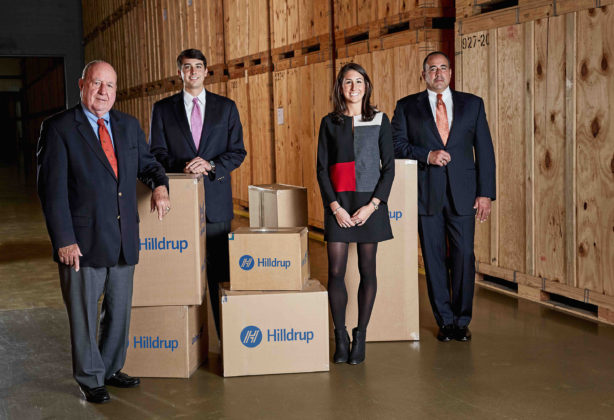 Charles G., Charlie, Jordan, and Charles W. McDaniel posing in a storage warehouse surrounded by moving boxes