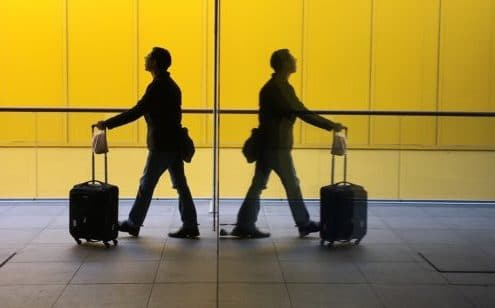 Two travelers walk in an airport
