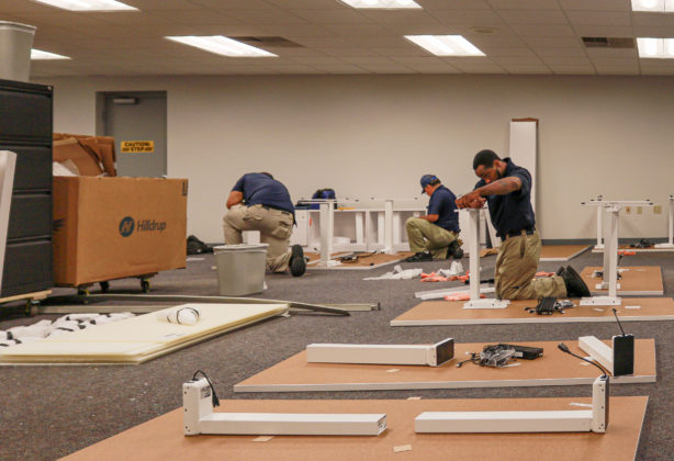 Hilldrup Commercial team members putting a cubicle together