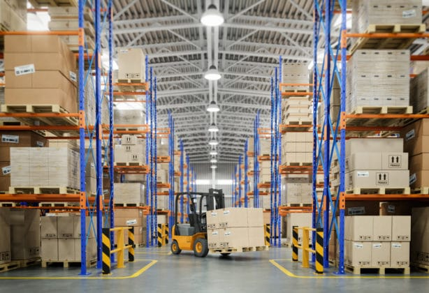 Forklift truck in warehouse or storage and shelves with cardboard