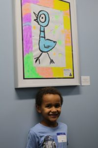 A young student poses with his artwork on display