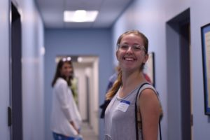 A student smiles while walking down the hallway