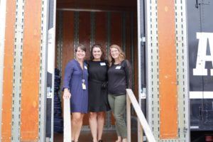 Three women pose at the entrance of one of Hilldrup's trucks during a tour