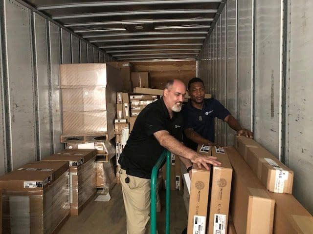 Two team members unload contents from moving truck.