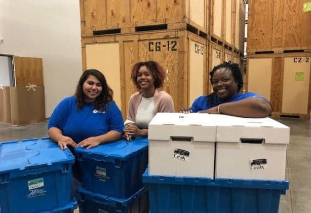 3 Hilldrup team members assist with moving items in Hilldrup's warehouse facility