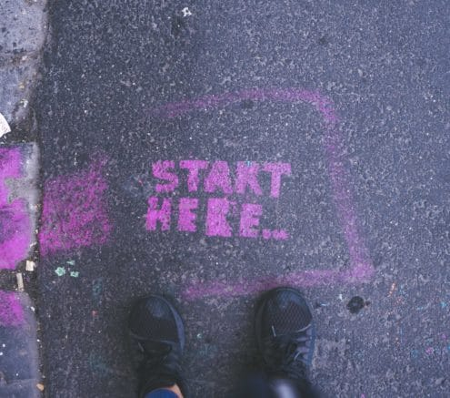 """Start here"" spraypainted in pink on the road with a person's feet at the ""start here"" wording"