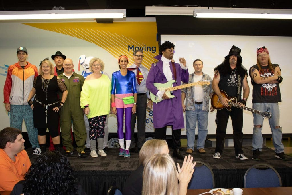 senior leadership group dressed in 80s gear for Halloween