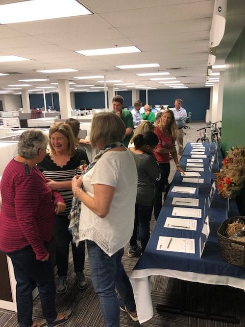 employees gathered around silent auction items for fundraiser for Rappahannock United Way
