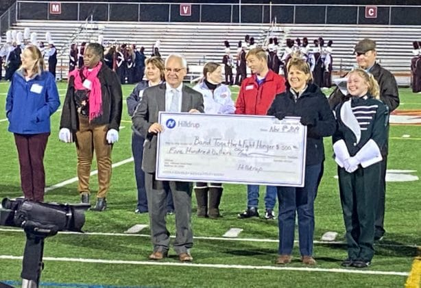 Mary Katherine Wood presents a large check to Band Together to Fight Hunger in Stafford